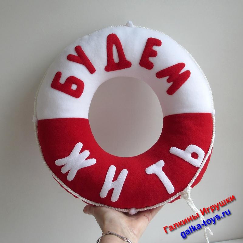 Сшита из красного и белого флиса, наполнена холлофайбером. Буквы - аппликация, отделка по периметру - бельевой шнур.