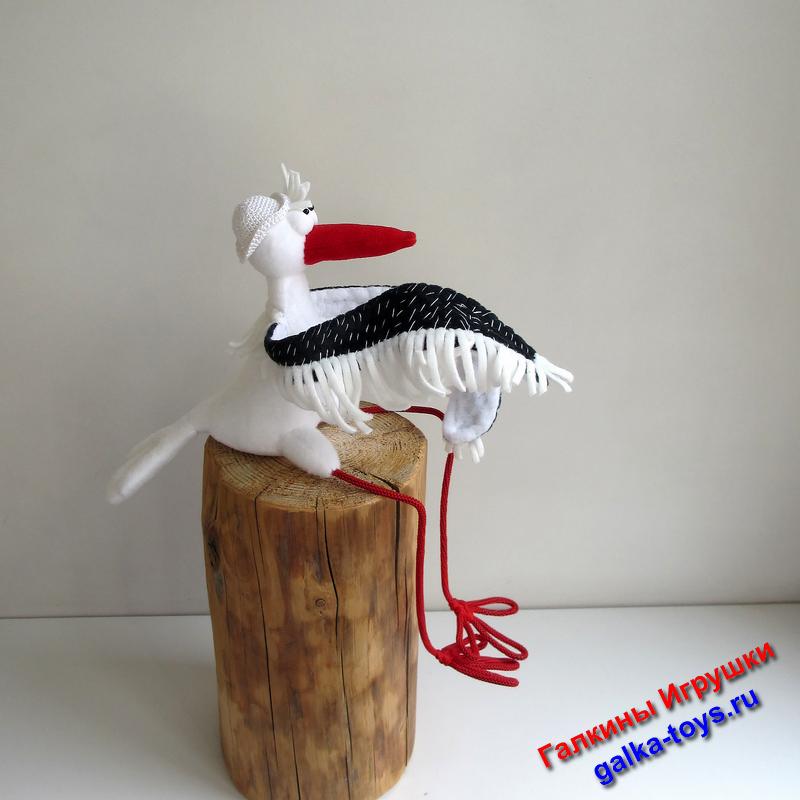 Эта игрушка красивая птица сшита из флиса, тело из белого, крылышки из черного на проволочном каркасе, а клюв из красного.